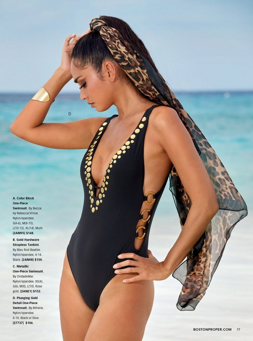 model wearing a black one-piece swimsuit with a plunging neckline lined with gold hardware and a leopard scarf in her hair.
