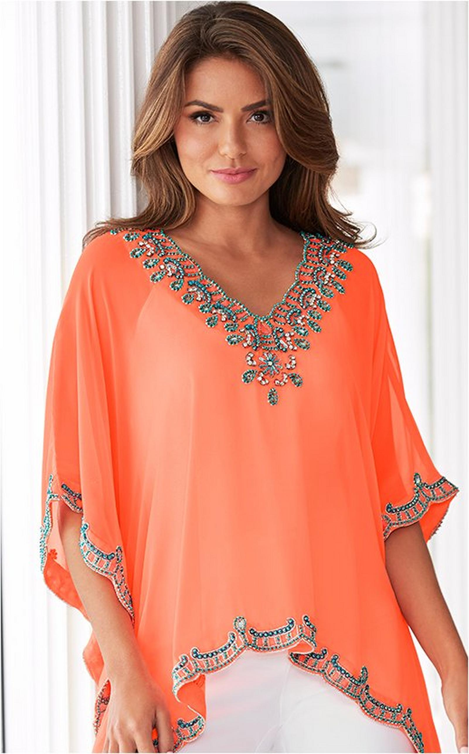 model wearing a coral embellished v-neck poncho, scoop-neck cami, and white cotton sateen crop pants.