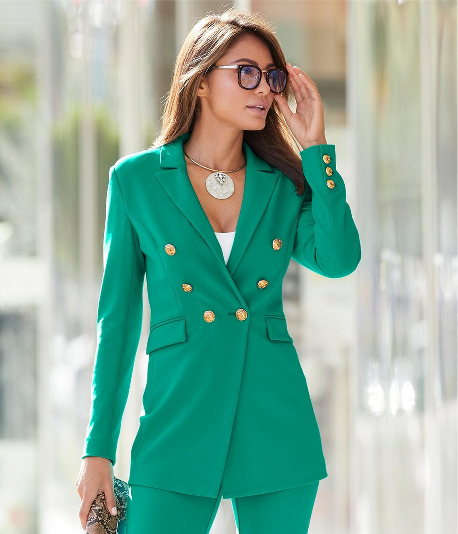 model wearing a jadeite double-breasted blazer, white tank top, jadeite pants, an opal choker necklace, and glasses.
