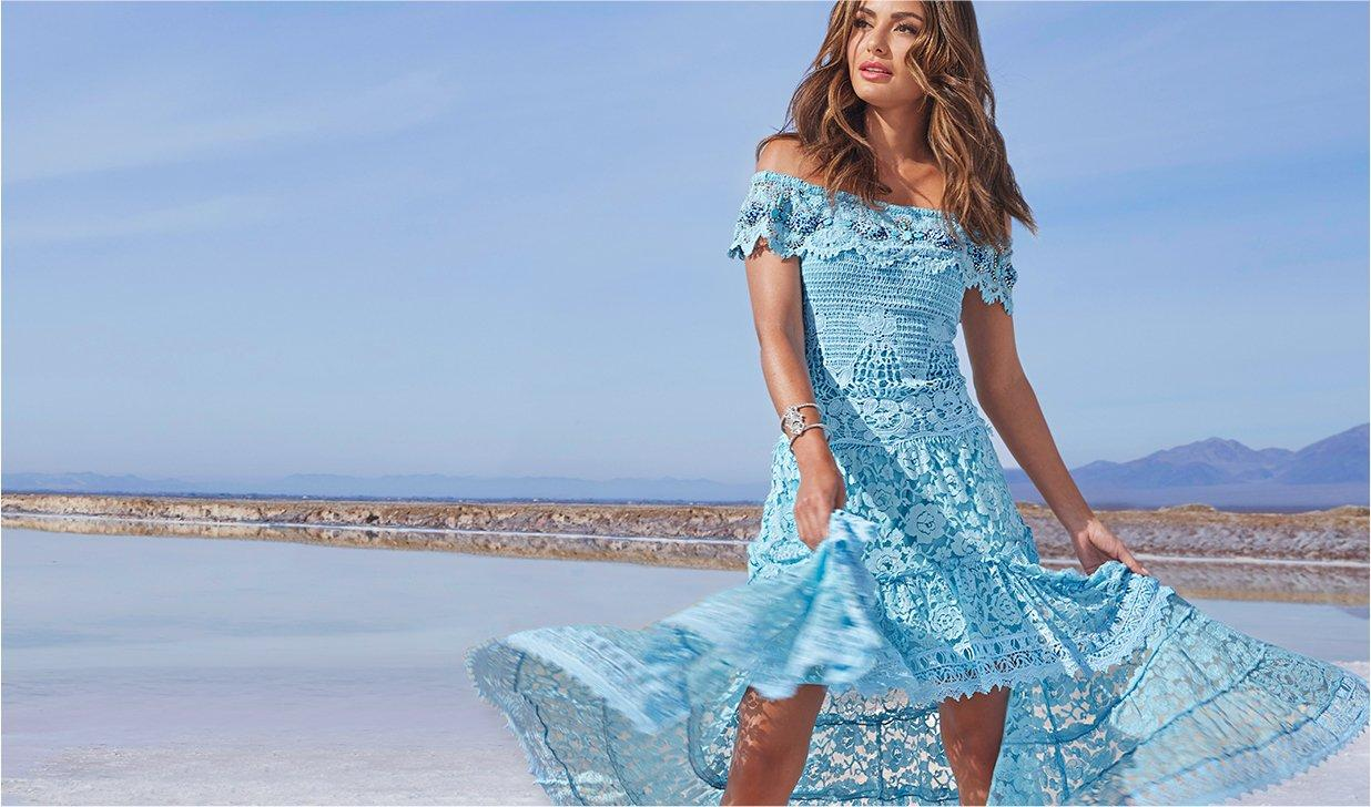 model wearing a blue lace off-theshoulder high-low maxi dress.