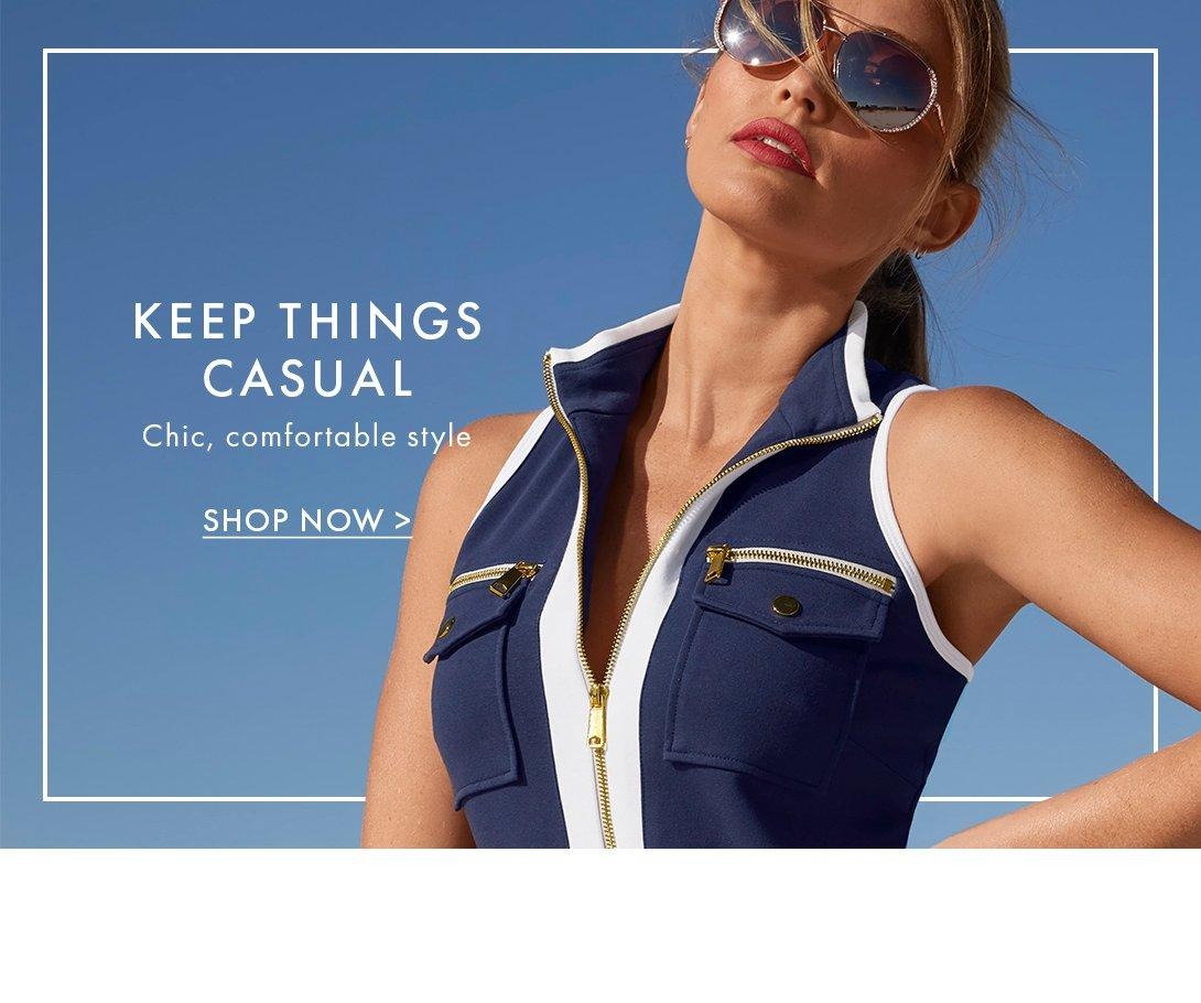 model wearing a sleeveless chic zip collared top in navy and white and sunglasses.