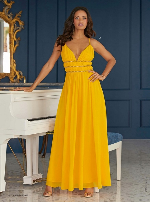 model wearing a yellow embellished maxi dress while standing next to a white piano.