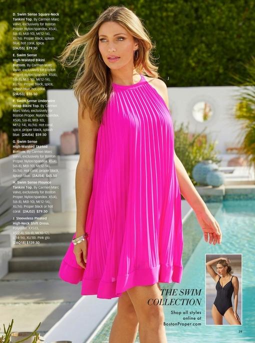 model wearing a neon pink sleeveless pleated high-neck shift dress.