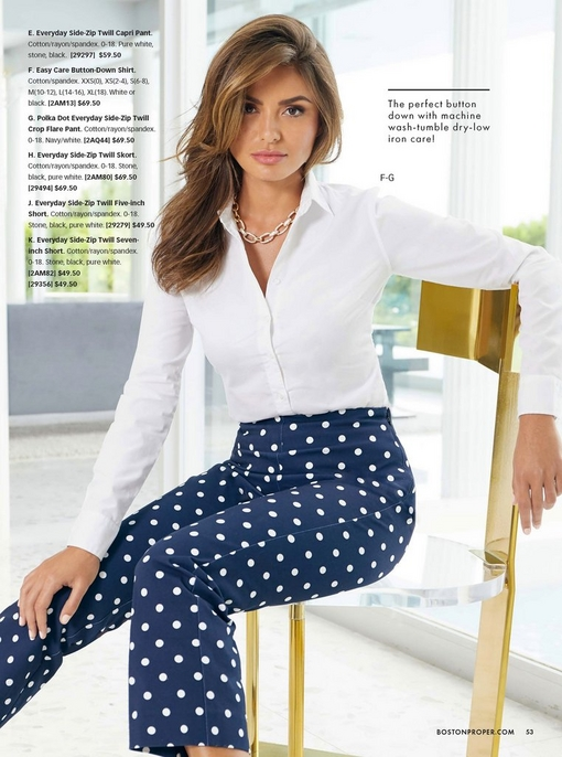 model wearing a white button-up long-sleeve top, a gold chain necklace, and blue and white polka-dot crop twill pants.