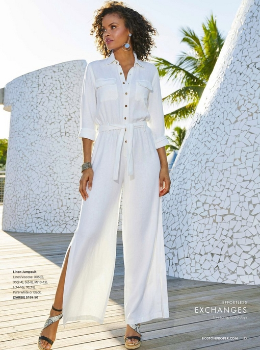 model wearing a white linen jumpsuit with slits on the leg and snake print wedges.