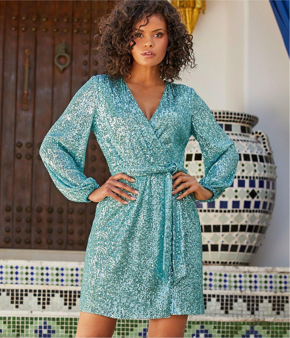 model wearing a blue sequin long-sleeve tie-waist dress.