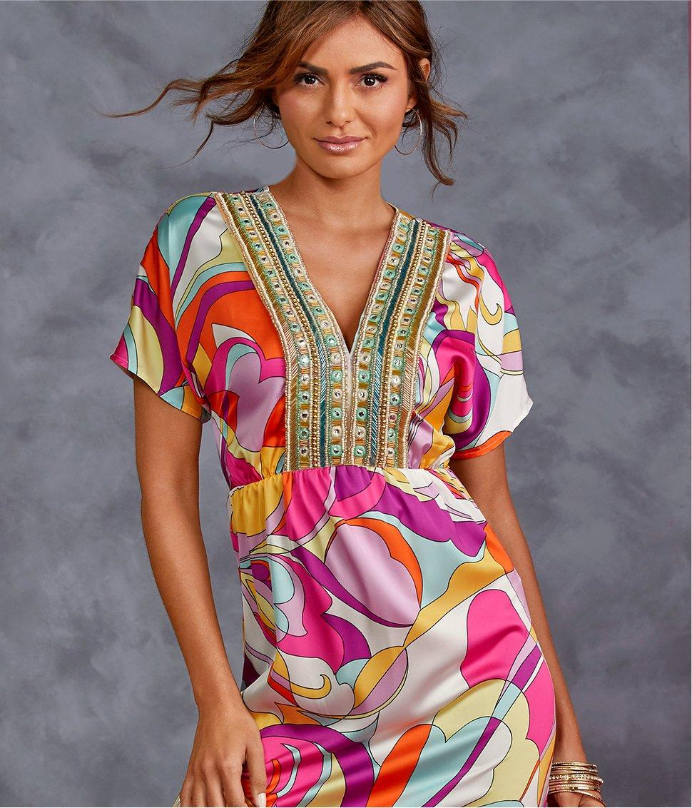 model wearing a multicolored paisley print maxi dress with a gold embellished neckline.