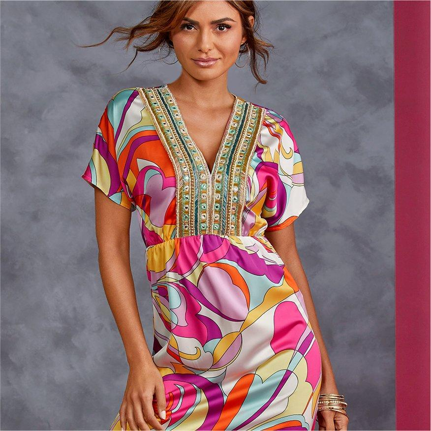 model wearing a multicolored paisley print dress with a gold embellished neckline.