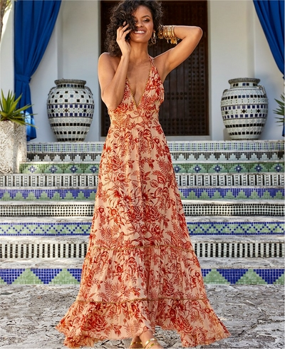 model wearing a tan and red floral printed maxi dress.