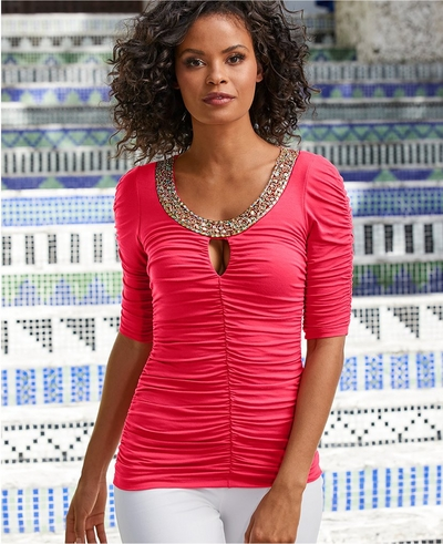 model wearing a pink ruched keyhole top with a jewel embellished neckline and white pants.
