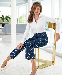 model wearing a white button down shirt, blue and white polka dot capri pants, and white heels.