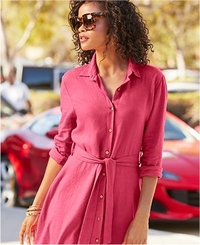 model wearing a pink linen shirtdress with a tie waist and sunglasses.