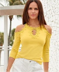 model wearing a yellow lace cold-shoulder top and white cargo pants.