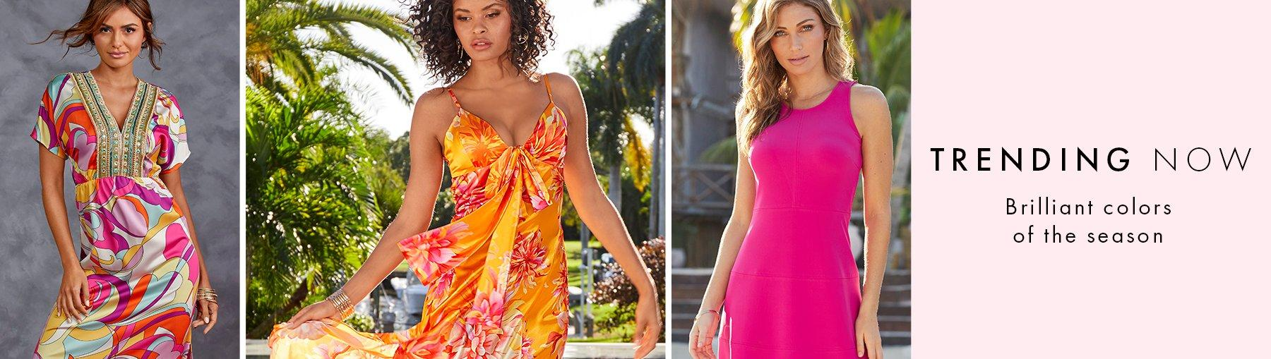 left model wearing a multicolored paisley print dress with gold embellished neckline. middle model wearing an orange and pink floral printed maxi dress. right model wearing a pink sleeveless dress.
