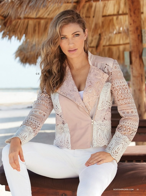 model wearing a blush and white lace jacket, white tank top, and white jeans.