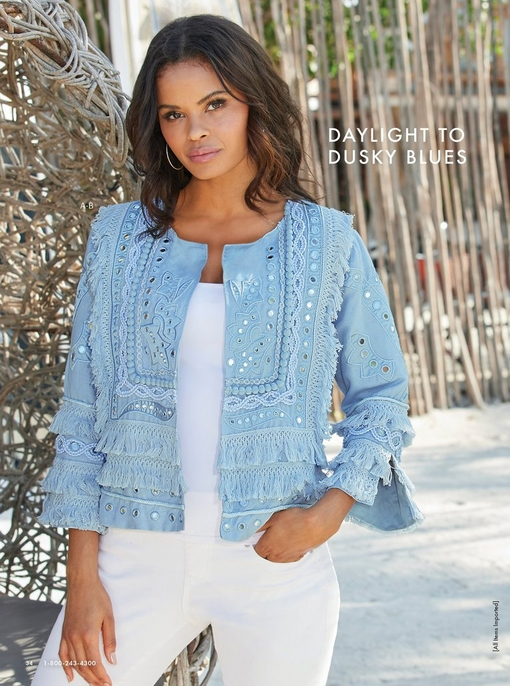 model wearing a light blue fringe and mirrored jacket, white tank top, white jeans.