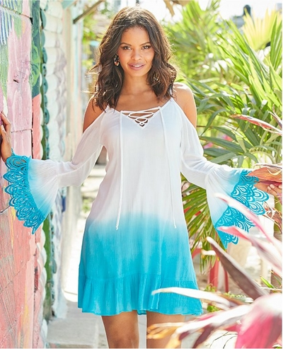model wearing a white and blue dip dyed lace embellished flare sleeve dress with a lace-up neckline.
