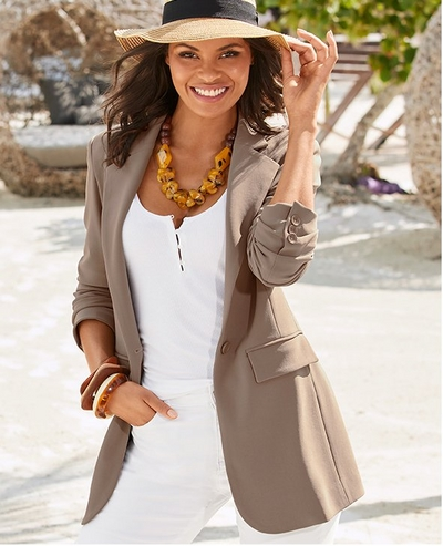model wearing a taupe blazer, white henley tank top, white pants, raffia hat, and orange stone necklace.