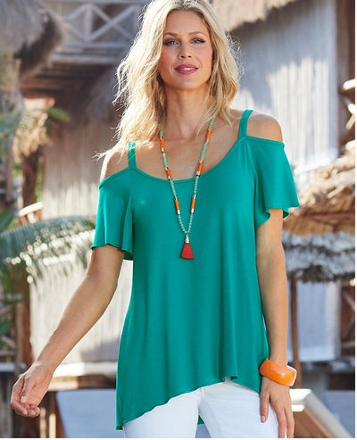 model wearing a teal cold-shoulder flutter sleeve top, white jeans, and an orange and green tassel necklace.