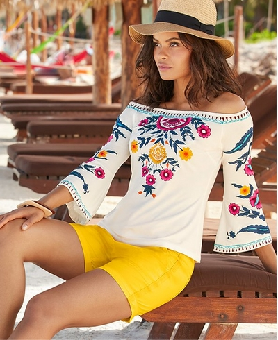 model wearing a white off-the-shoulder flare sleeve top with floral embroidery, yellow cargo shorts, and a raffia hat.