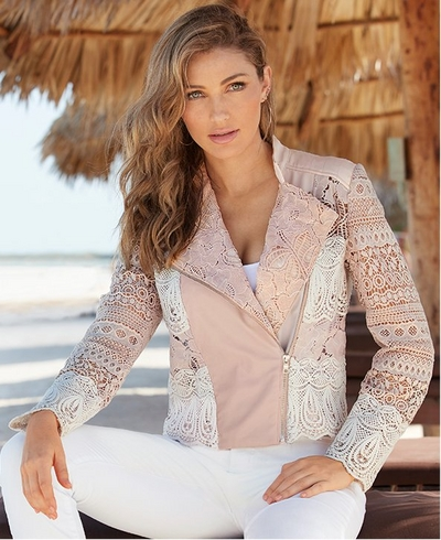 model wearing a blush and white lace detail jacket, white tank top, and white jeans.