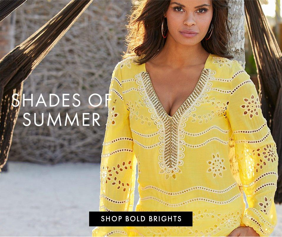 model wearing a yellow eyelet tunic top with a gold embellished neckline.