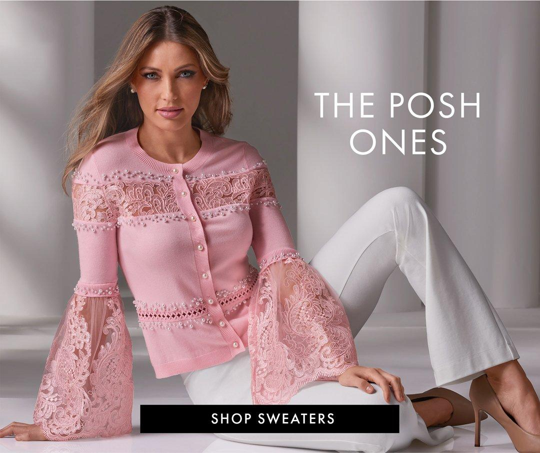 model wearing a pink lace and pearl flare-sleeve button down cardigan, white bootleg pants, and nude pumps. right text: the posh ones. shop sweaters.