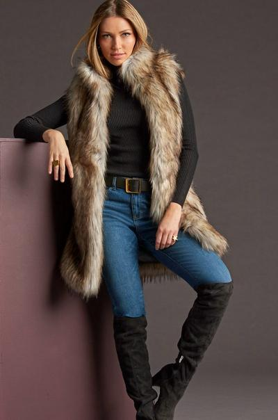 model wearing a long faux-fur vest, black turtleneck sweater, jeans, and black over-the-knee boots.