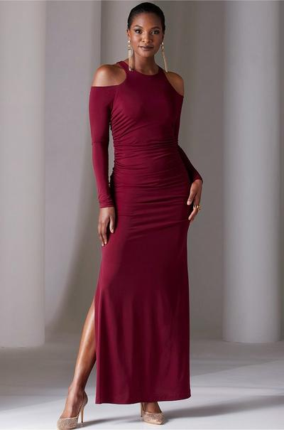 model wearing a wine colored cold-shoulder long-sleeve maxi dress, diamante pumps, and gold chain earrings.