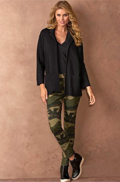 model wearing a black sweater jacket, black v-neck tee shirt, studded camo printed jeans, and black sneaker wedges.