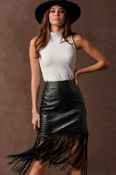 model wearing a white sleeveless turtleneck top, faux-leather croc print skirt with fringe details, and a black felt hat.