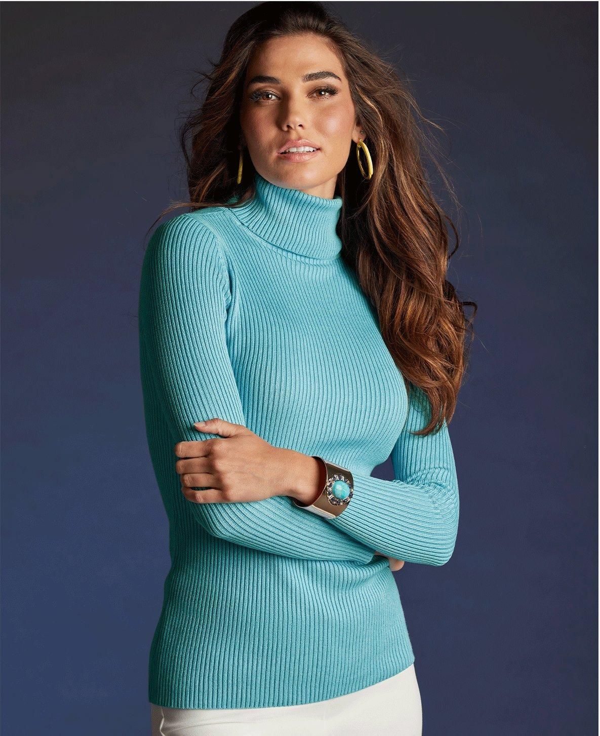 model wearing a light blue ribbed turtleneck sweater, gold hoop earrings, and white pants.