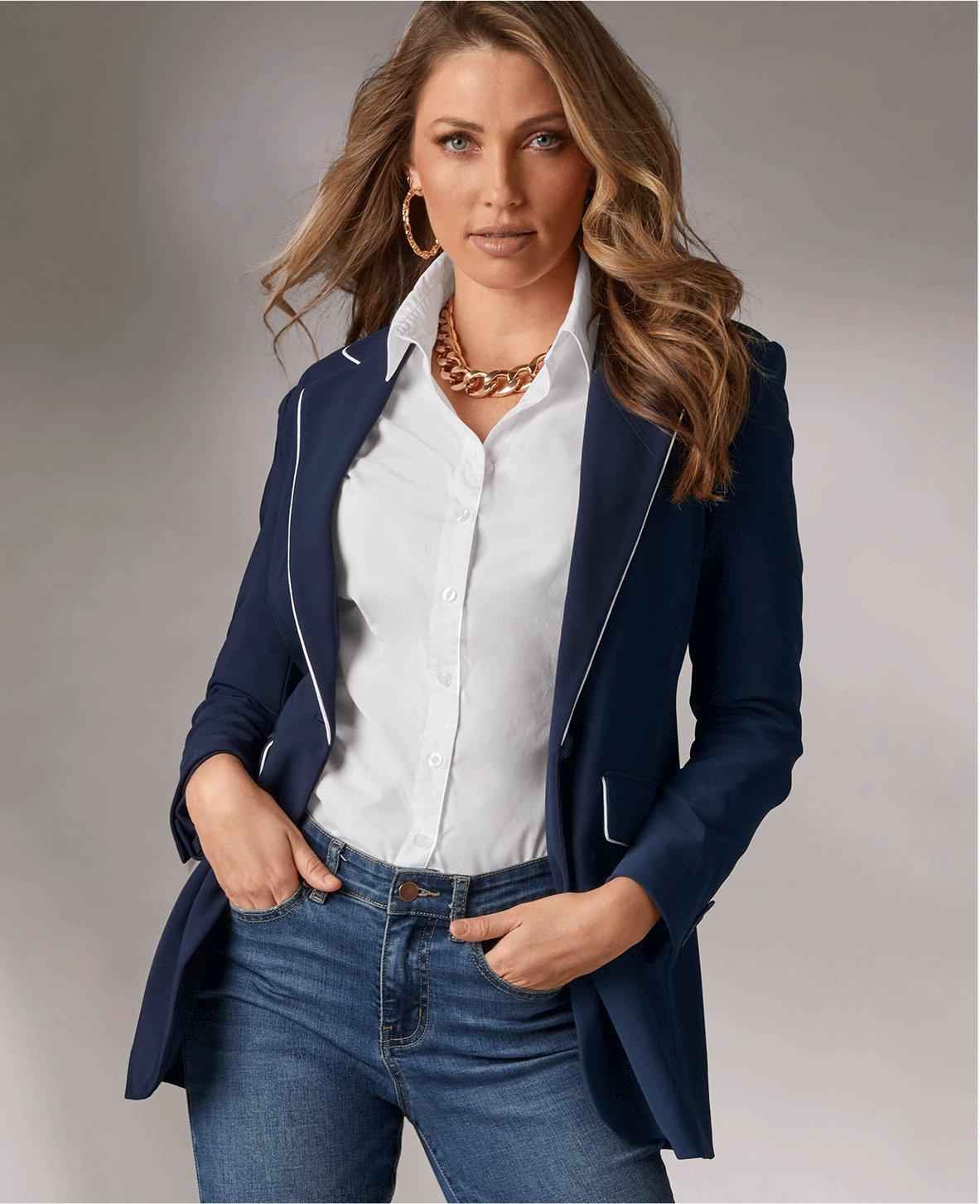 model wearing a navy blazer with white piping, white button-up shirt, chunky gold chain link necklace, gold chain link hoop earrings, and jeans.