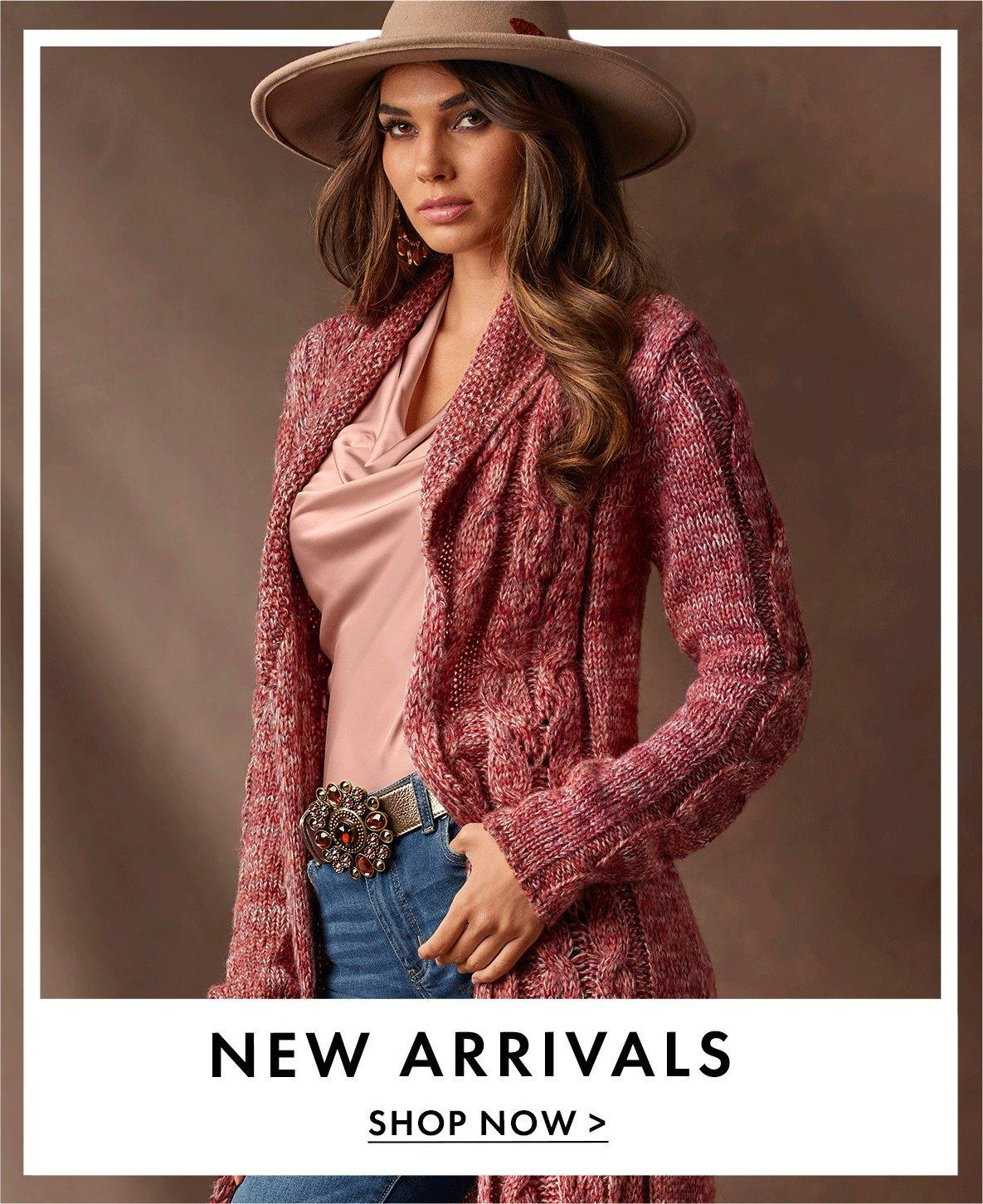 model wearing a pink cable marled sweater duster, light pink cowl neck top, brown jeweled belt, jeans, and taupe felt hat.