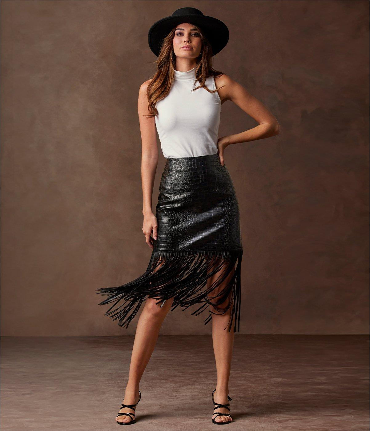 model wearing a white sleeveless turtleneck top, black hat, black crocodile skirt with fringe, and black strappy heels.