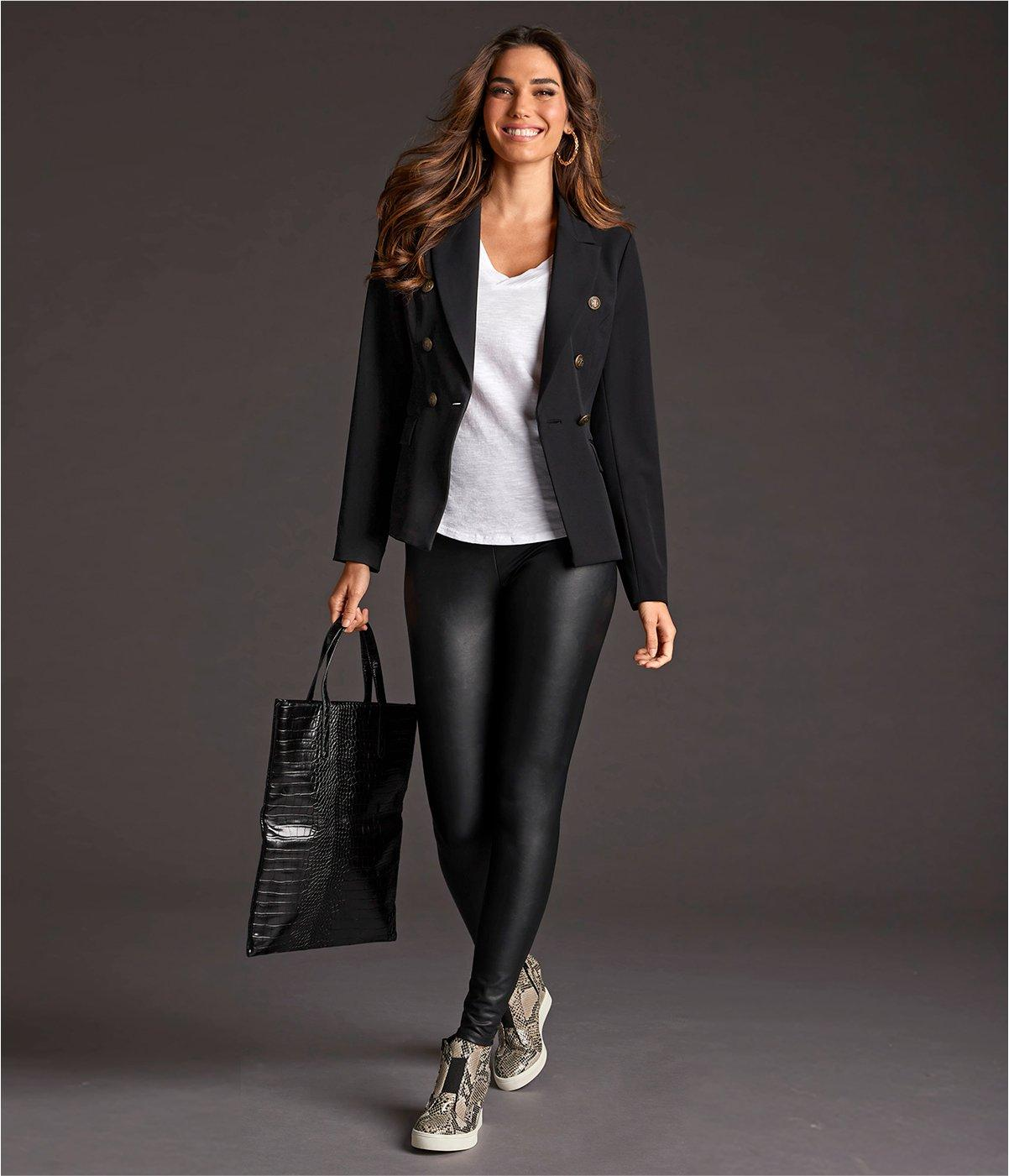 model wearing a black double-breasted blazer, white v-neck tee, black faux leather leggings, snakeskin print sneaker wedges, and a black crocodile bag.