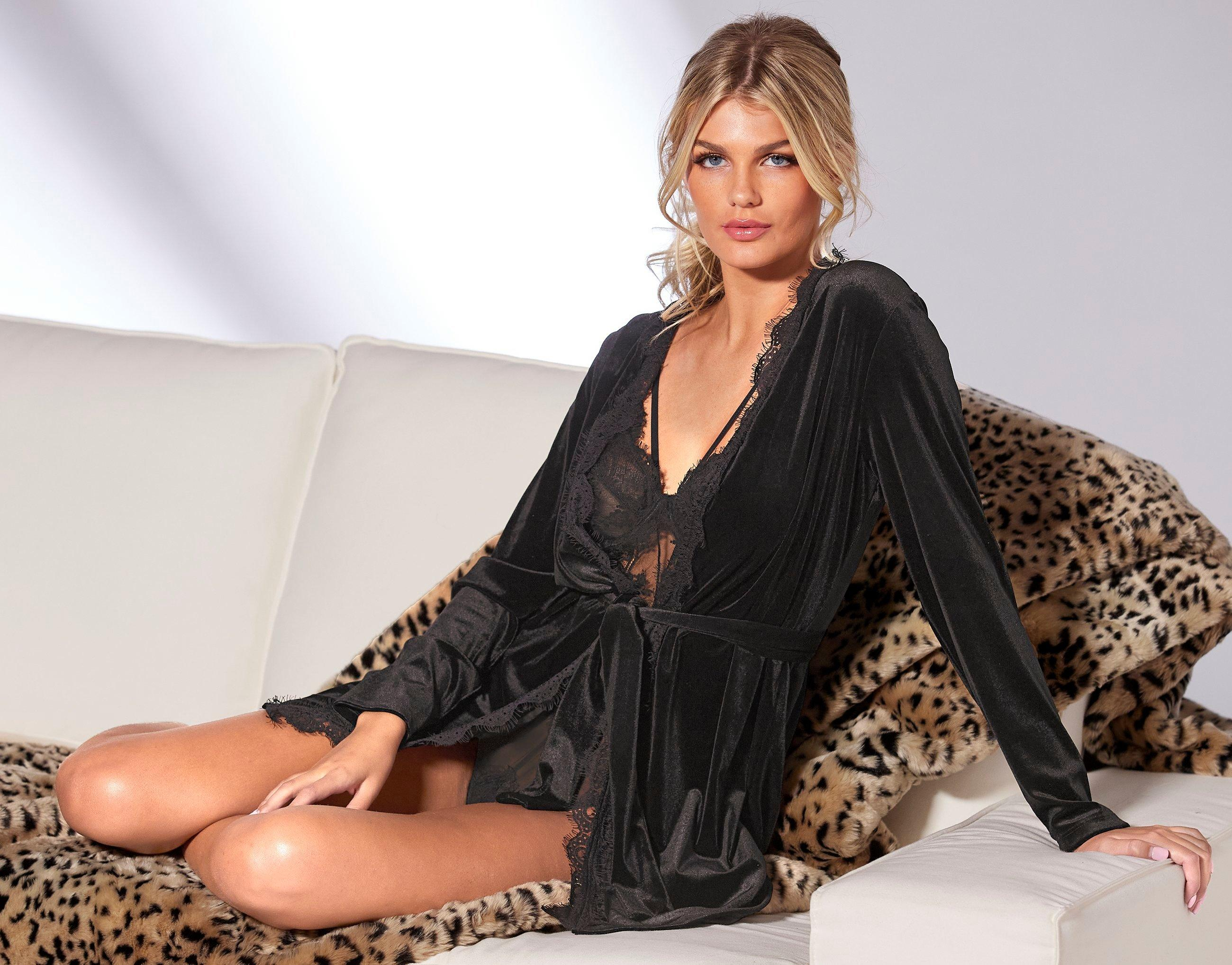 model wearing a black lace velour robe and a black strappy lace bodysuit laying on top of a leopard faux fur throw.