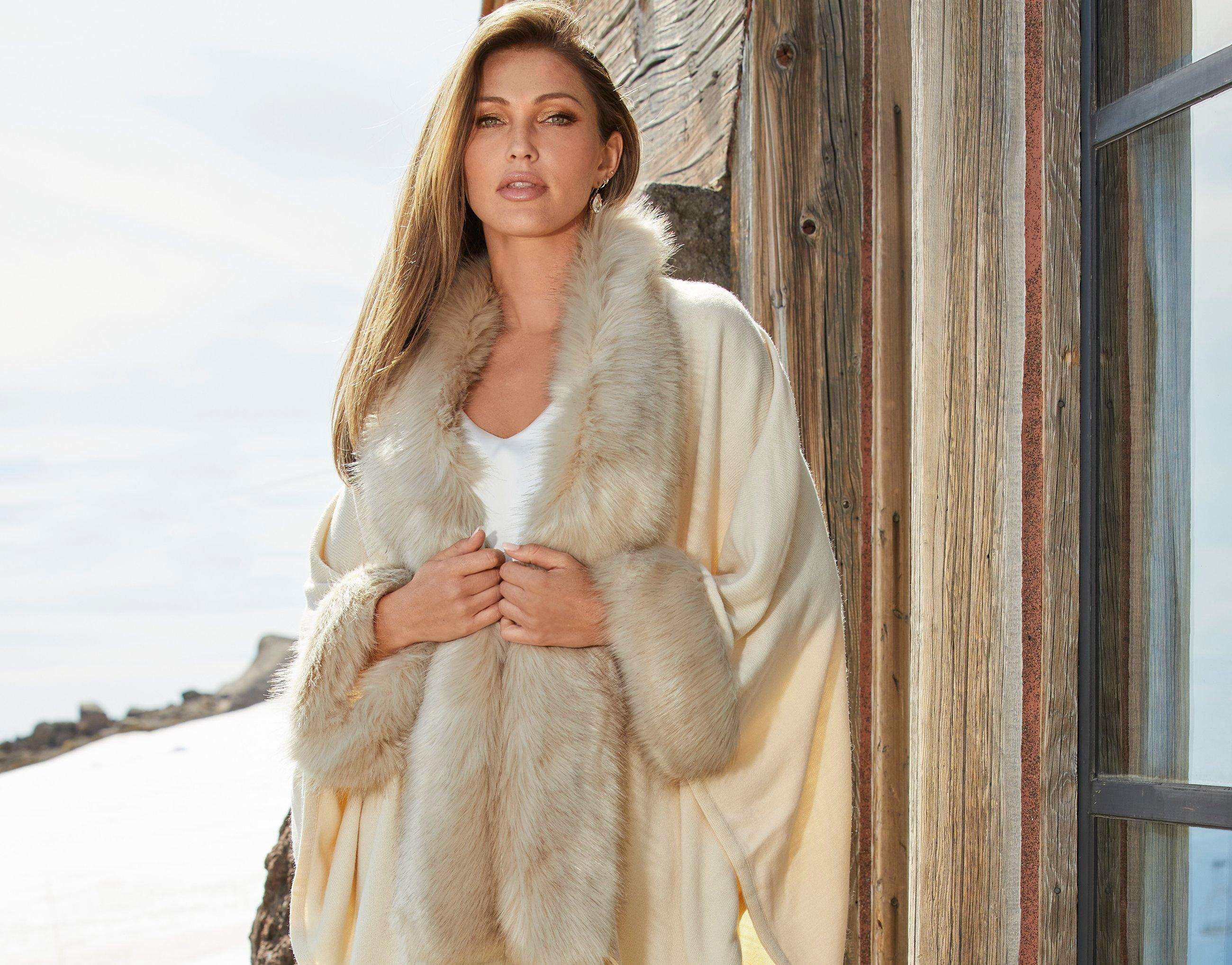 model wearing a beige faux fur poncho and white v-neck sleeveless top.