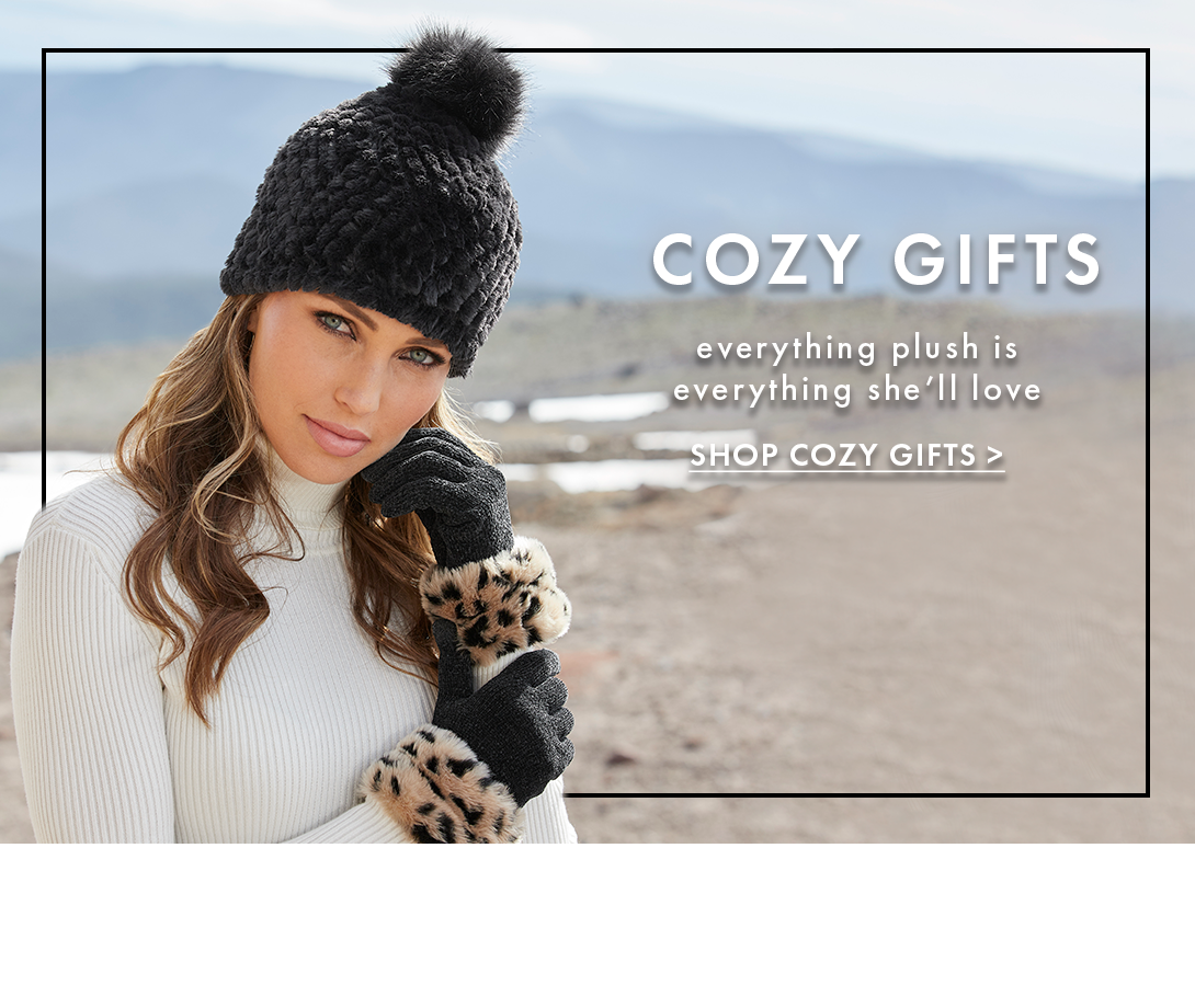 model wearing a black beanie faux fur hat, black and leopard gloves, and white turtleneck sweater. text: cozy gifts. everything plush is everything she