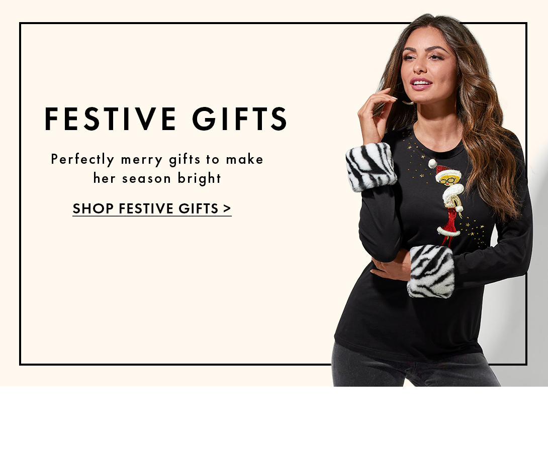 model wearing a black mrs. claus sweater with faux fur zebra cuffs. text: festive gifts. perfectly merry gifts to make her season bright. shop festive gifts.