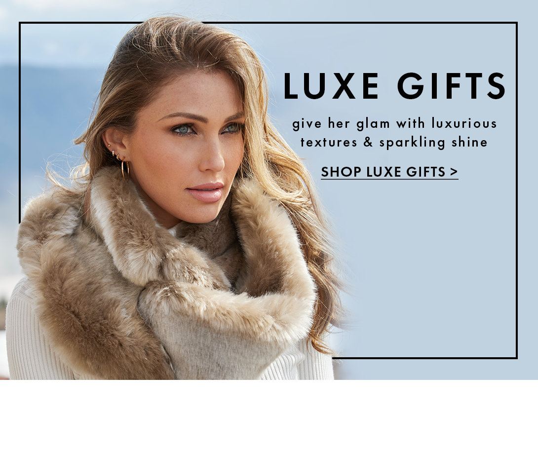 model wearing a beige faux-fur infinity scarf and white sweater. text: luxe gifts. give her glam with luxurious textures & sparkling shine. shop luxe gifts.