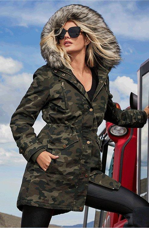 model wearing a camouflage faux-fur coat, faux-leather black leggings, and sunglasses.
