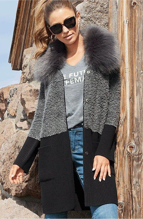 model wearing a gray and black color-block faux-fur sweater coat, gray v-neck tee, jeans, and sunglasses.