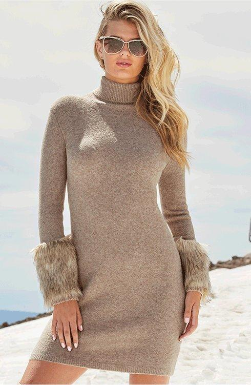 model wearing a tan turtleneck sweater dress with faux fur cuffs and sunglasses.
