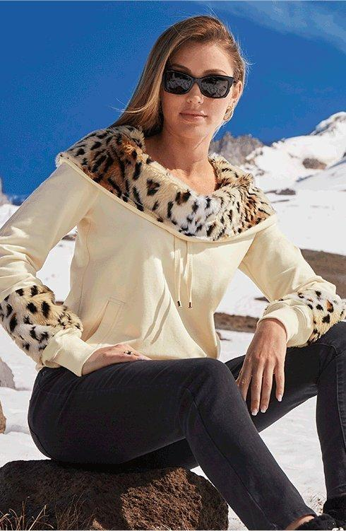 model wearing a beige off-the-shoulder sweatshirt with leopard faux fur touches, black pants, and sunglasses.