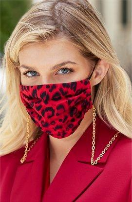 model wearing a red and black leopard print face mask with a gold chain and a red blazer.