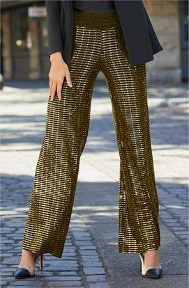 model wearing a black and gold striped palazzo pants.