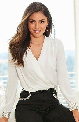 model wearing a white pearl embellished cuff surplice top and black pearl embellished jeans.