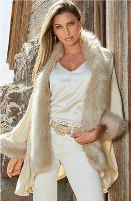 model wearing a white and beige faux-fur poncho, white v-neck top, gold jeweled belt, and white jeans.