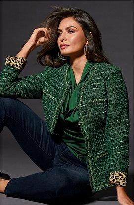 model wearing a green and gold tweed jacket, green cowl neck top, and jeans.